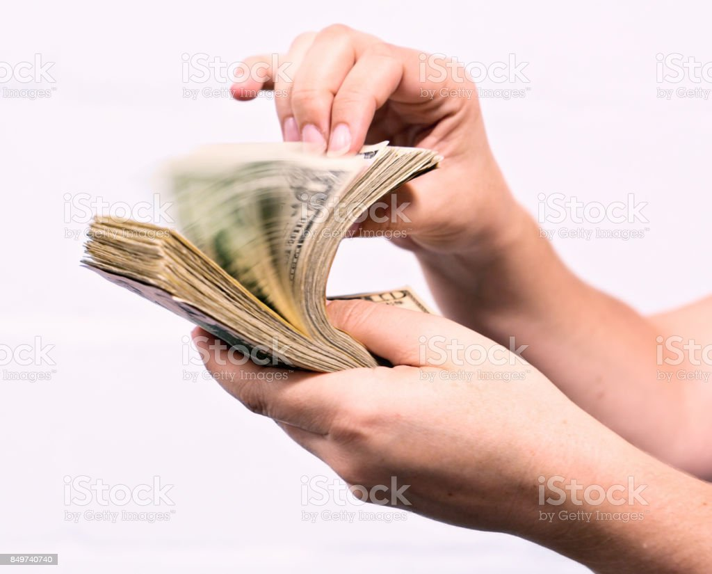 Female hand flipping through fistful of dollars stock photo