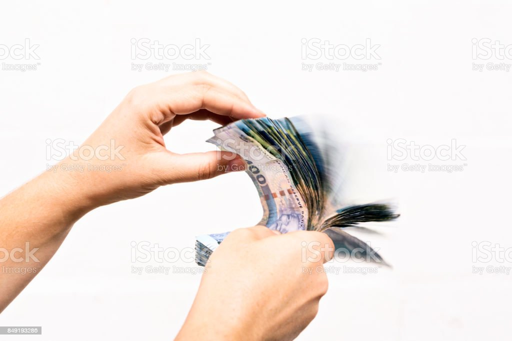 Female hand flips through thick bundles of South African banknotes stock photo