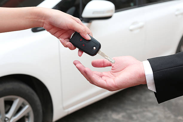 female hand giving a key for buyer or rental car. - used car selling stock pictures, royalty-free photos & images