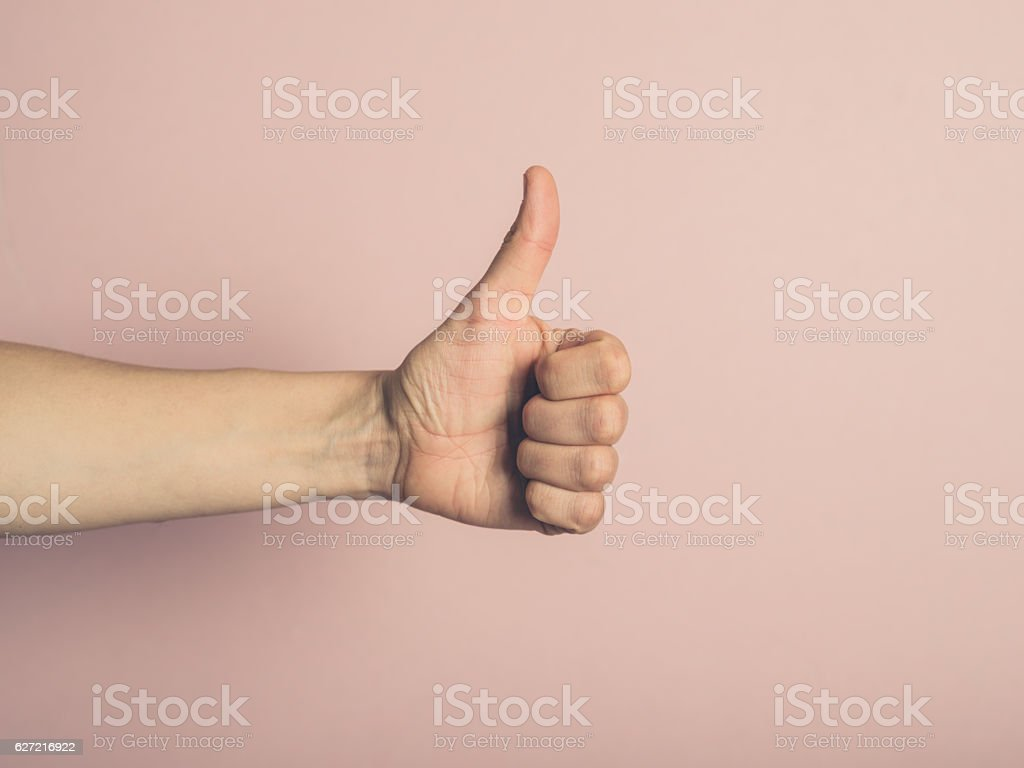 Female hand giving thumbs up stock photo