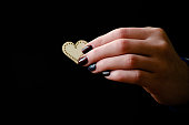 istock Female hand giving wooden heart on the black background 1127546707