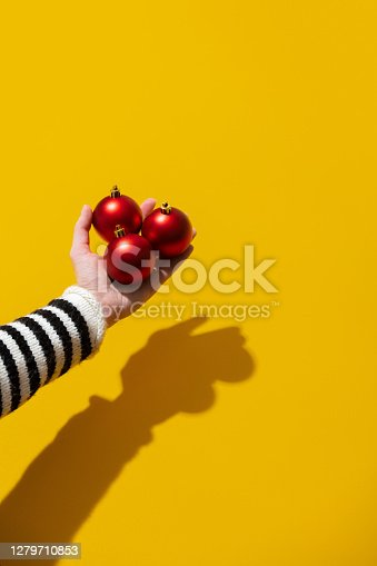 Female hand hold Christmas baubles on yellow background