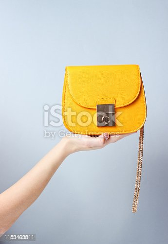 istock Female hand hold fashionable yellow leather bag with golden chain on gray background. 1153463811