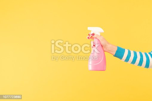 istock female hand hold sprayer yellow cleaning housework 1077723890