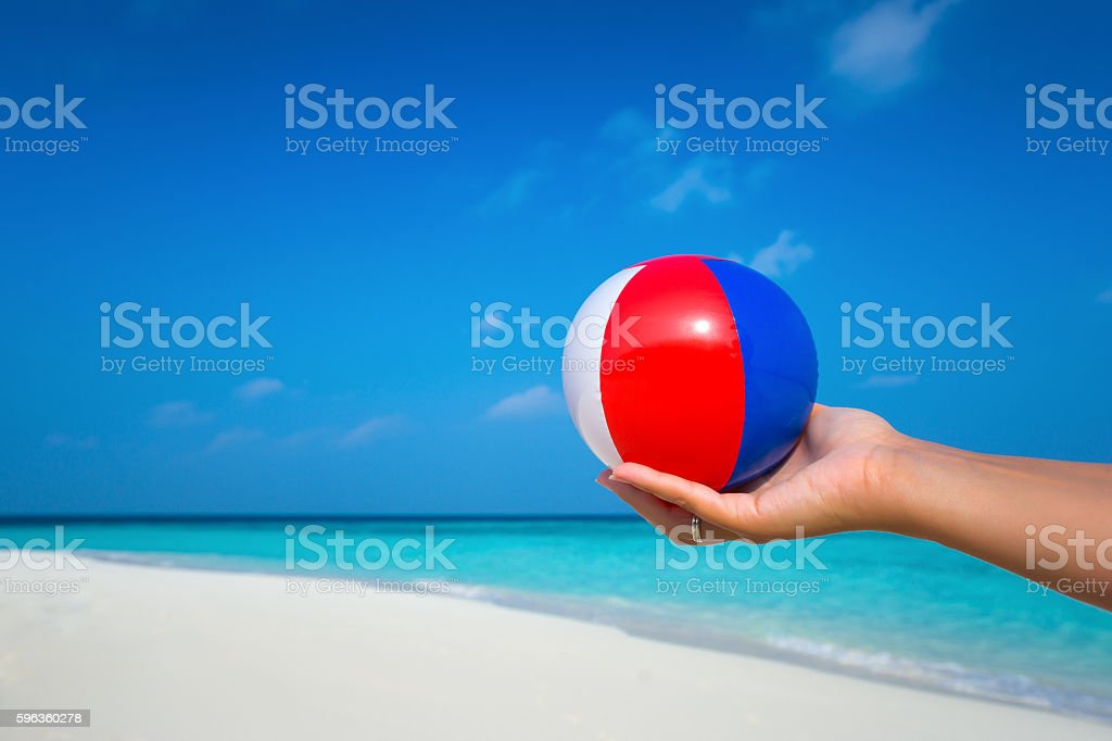 female hand holding a ball at a beautiful beach royalty-free stock photo