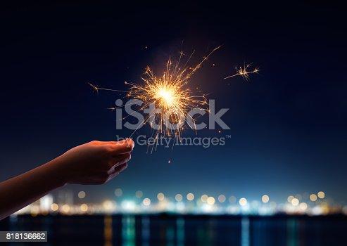 istock Female hand holding a burning sparkler 818136662