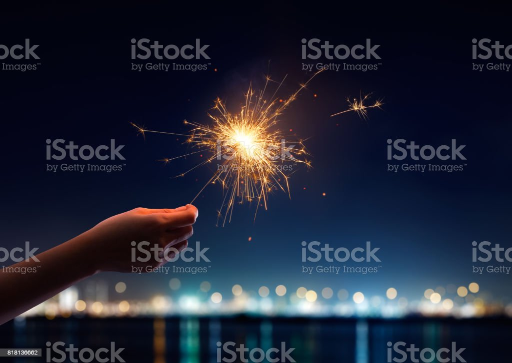 Female hand holding a burning sparkler stock photo