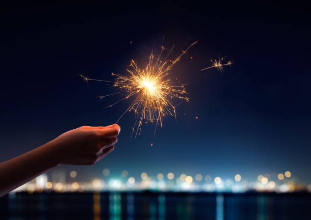 female hand holding a burning sparkler - sparkler stock pictures, royalty-free photos & images