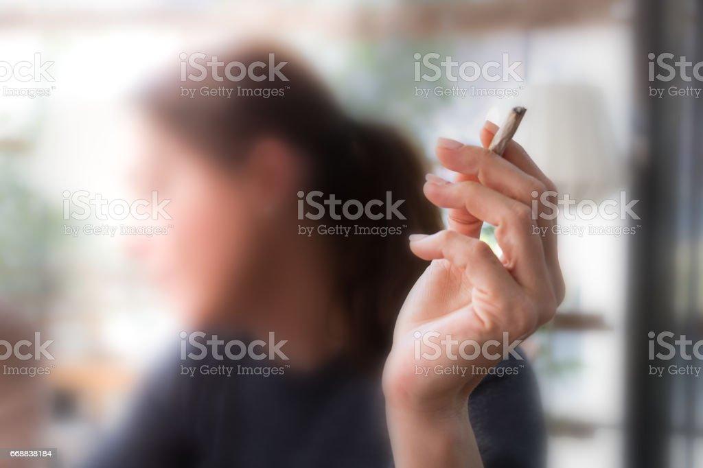 Feminino mão segurando um cigarro - foto de acervo