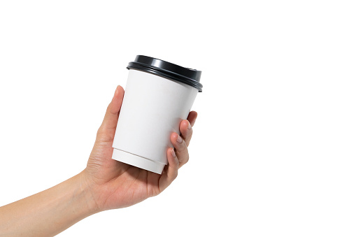 female hand holding a coffee paper cup isolated on white background.