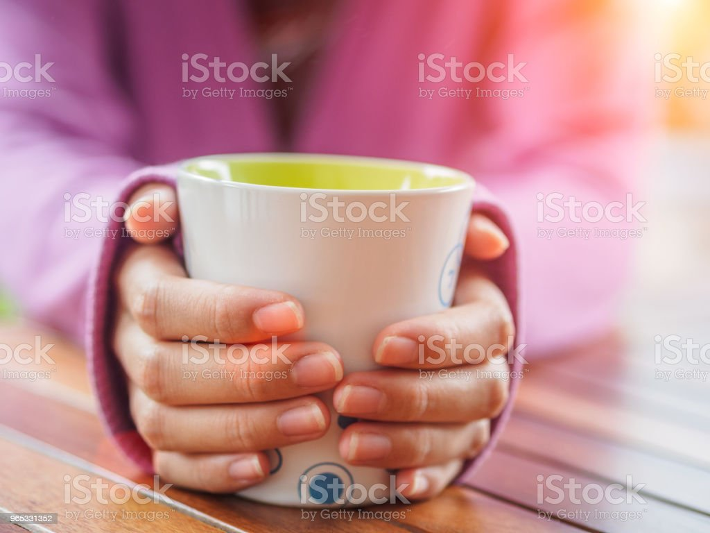 Female hand holding a cup on wooden table. royalty-free stock photo