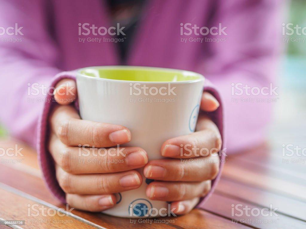 女性手拿著一個杯子在木桌上。 - 免版稅上衣圖庫照片