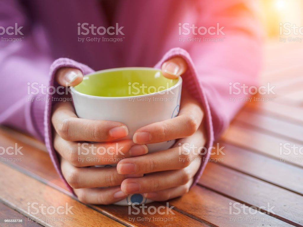 Female hand holding a cup on wooden table. zbiór zdjęć royalty-free