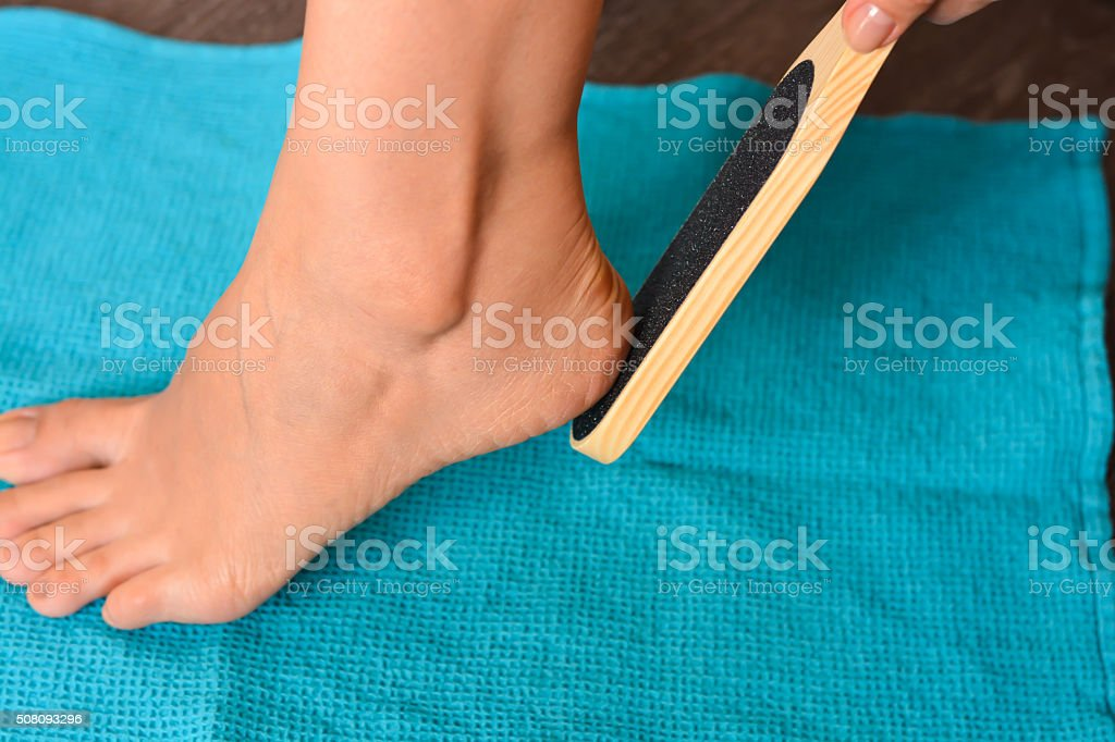 Female hand holding a foot file near her heel stock photo