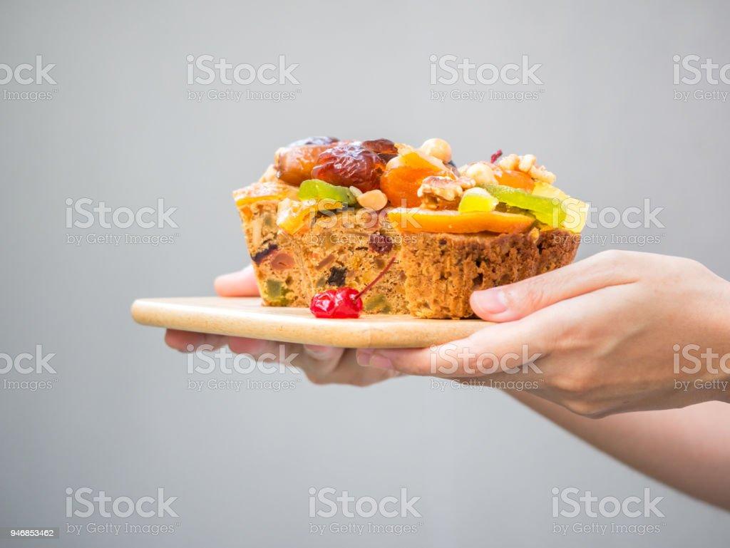 Weibliche Hand hält einen Laib Obstkuchen auf Holzteller mit grauem Hintergrund – Foto