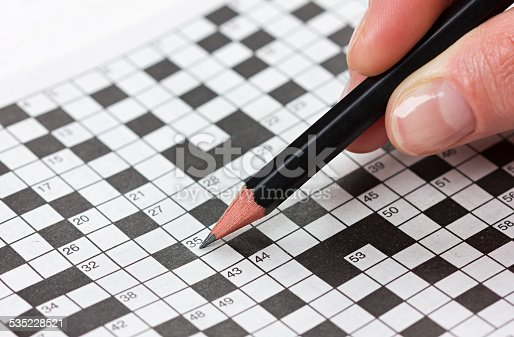 woman hand holding a pencil and solves crossword puzzle