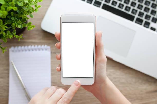 Weibliche hand hält das Telefon mit isolierten Bildschirm und laptop – Foto