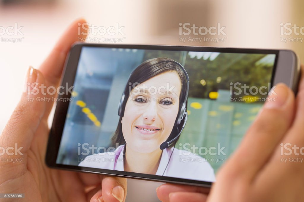 Female hand holding a smart phone during a skype video stock photo