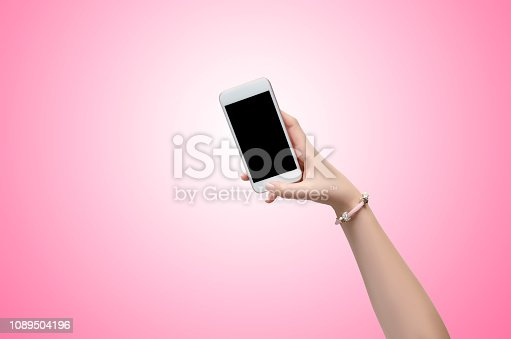 863476202istockphoto Female hand holding a smartphone over pink background 1089504196