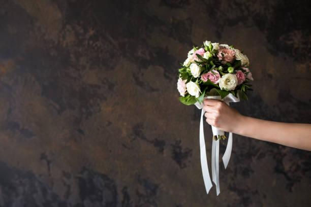 Female hand holding a wedding bouquet on a dark background picture id1261527846?b=1&k=6&m=1261527846&s=612x612&w=0&h=3dljhjnje5ic1zi5pljcbsnqwdzcp5aolo0gga smqu=