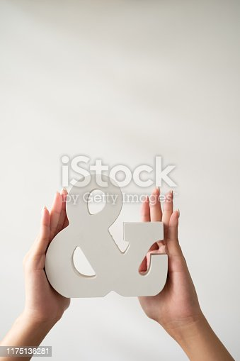 Female hand holding an ampersand in front of white background