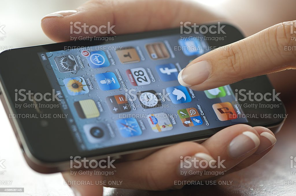 Female hand holding an Apple iPhone 4 royalty-free stock photo