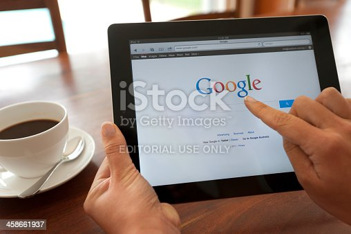Sydney, Australia - October 28, 2011: Female hand holding an ipad showing Google. She is touching the screen. There is coffee on the dining table in the background.  This image shows the ipad being used in a casual environment.