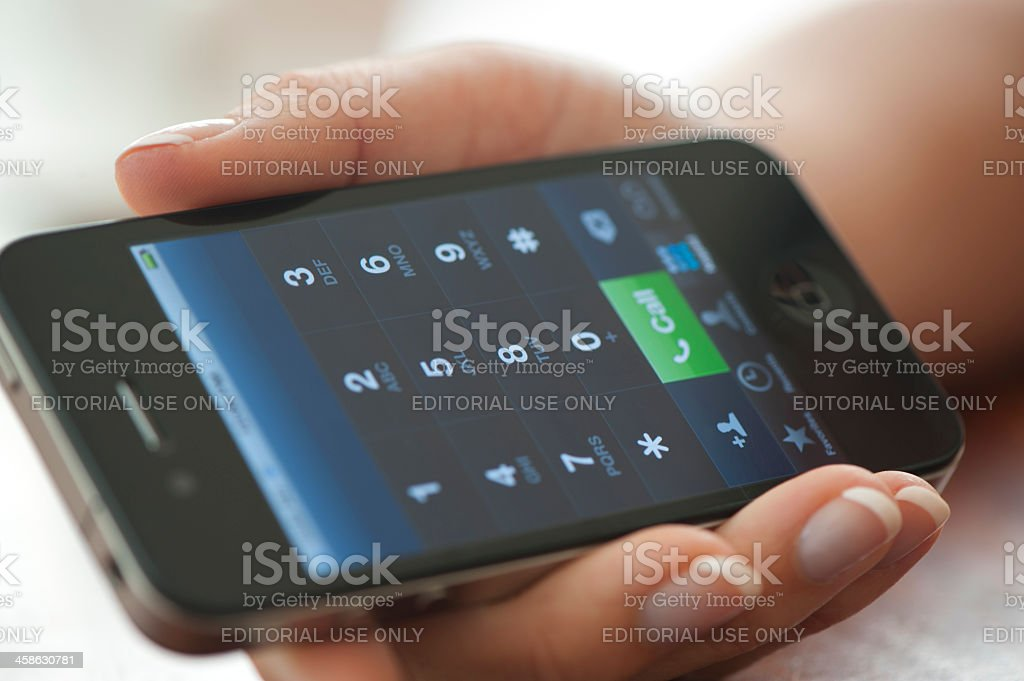 Female hand holding an iphone displaying the dialling interface stock photo