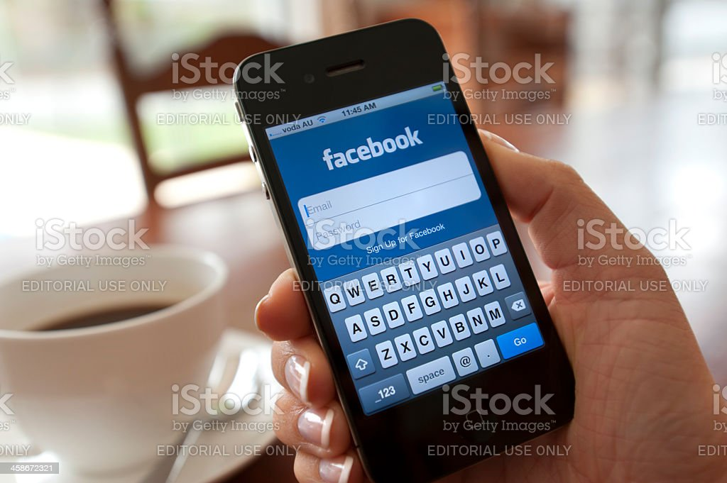 Female hand holding an iphone showing the Facebook login page royalty-free stock photo