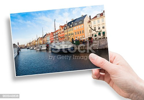 istock A female hand holding an postcard about a panoramic view of the Nyhavn city, one of the most famous landmark in Copenhagen, during the Christmas holidays with christmas ornament (Europe - Denmark) 955946808