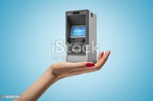 istock Female hand holding ATM machine on blue background 1183092501