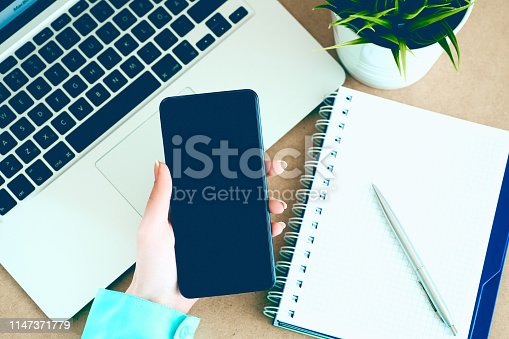 istock Female hand holding black mobile smart phone with blank screen on laptop computer and notepad background. 1147371779