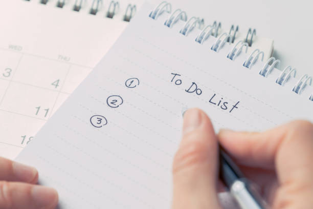 female hand holding black pen writing to do list prioritized by number on white paper notepad with desktop calendar date on white office table - to do list foto e immagini stock