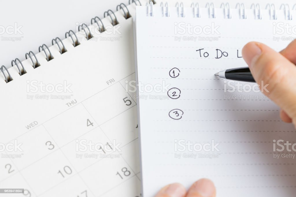 Female hand holding black pen writing To Do List prioritized by number on white paper notepad with desktop calendar date on white office table - Royalty-free Black Color Stock Photo