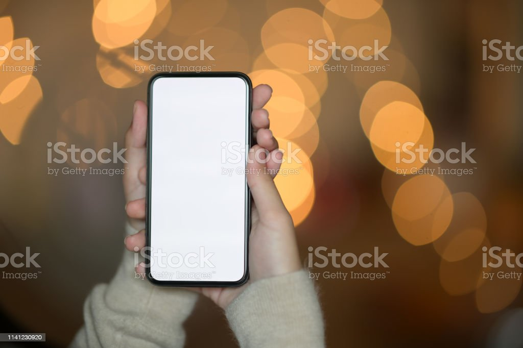 Female hand holding blank screen mobile phone at street night