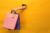istock Female hand holding bright shopping bags 870143200
