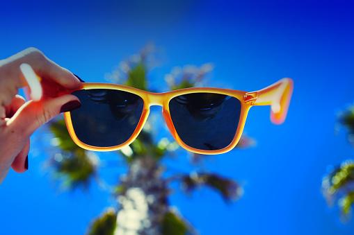 Female hand holding bright sunglasses against sunny sky