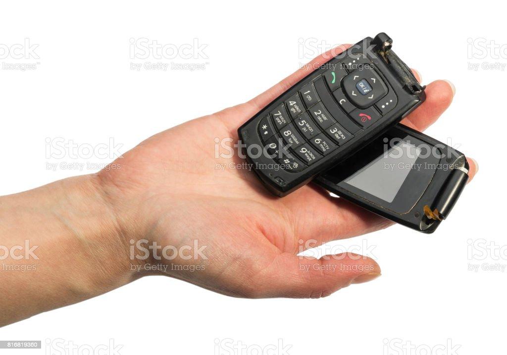 Female hand holding broken mobile phone isolated on white background. stock photo