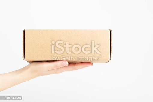 Female hand holding carton box. Food conveyance. Fast delivery service. Mockup style and place for text. Package and shipping concept. Isolated on white.