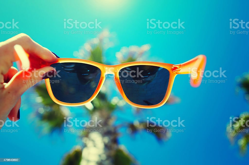 Female hand holding colorful sunglasses against palm tree stock photo