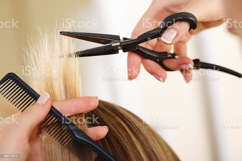 Female hand holding comb and hot thermal scissors cutting tips stock photo