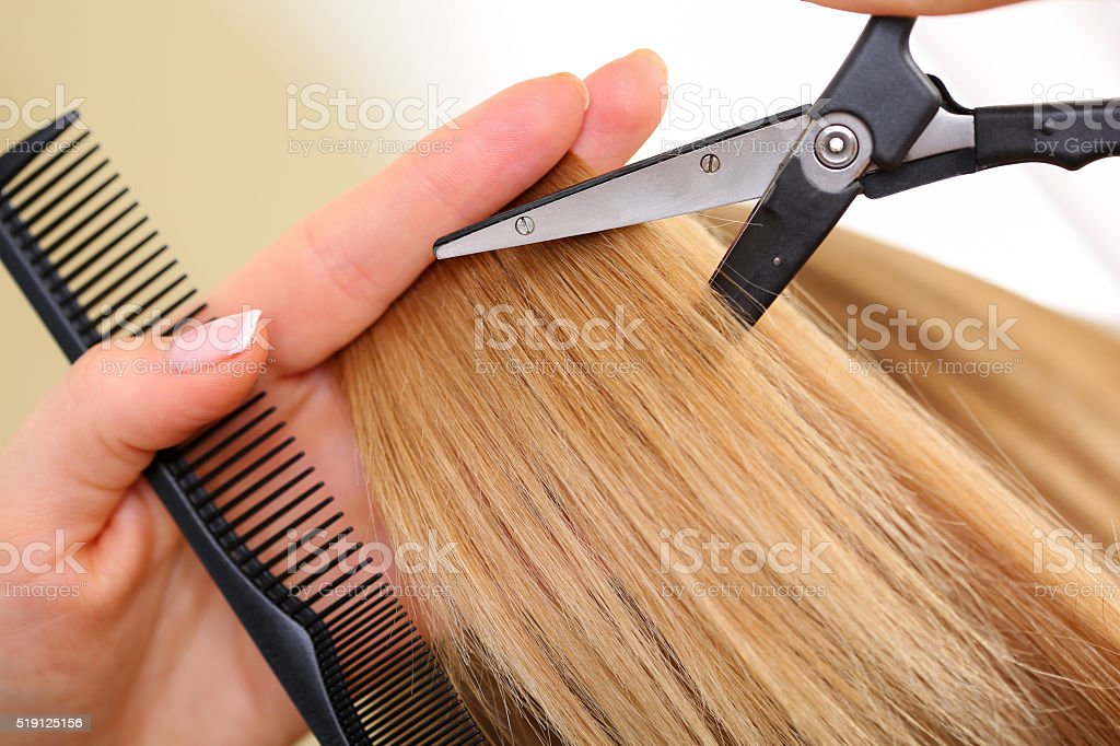 Female hand holding comb and hot thermal scissors stock photo