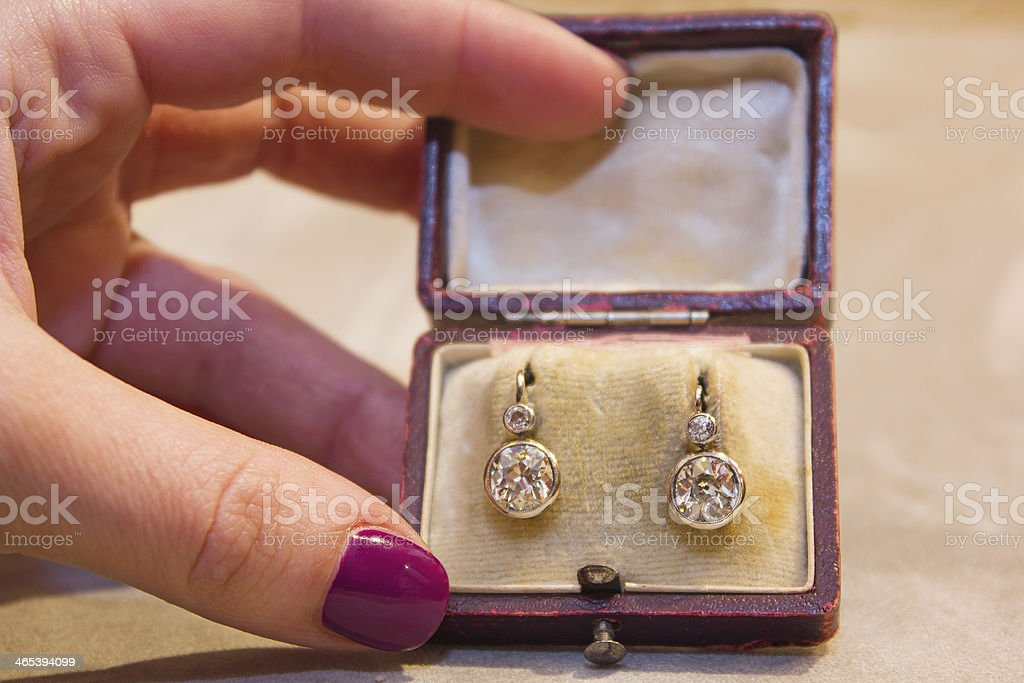 Female hand holding diamond earring in old box stock photo