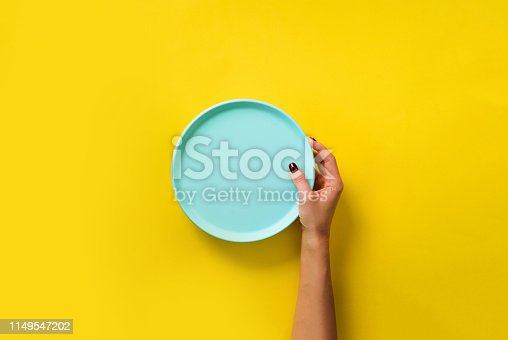 istock Female hand holding empty blue plate on yellow background with copy space. Healthy eating, dieting concept. Banner 1149547202