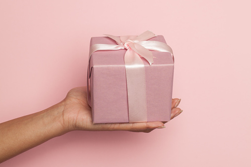 Female hand holding gift with silky ribbon on pastel pink background