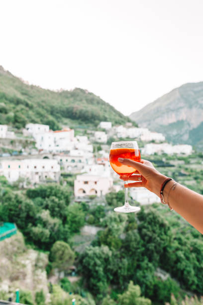 Weibliche Hand halten Glas mit Spritz Aperol Alkohol Getränk Hintergrund des schönen alten italienischen Dorf an der Amalfiküste – Foto