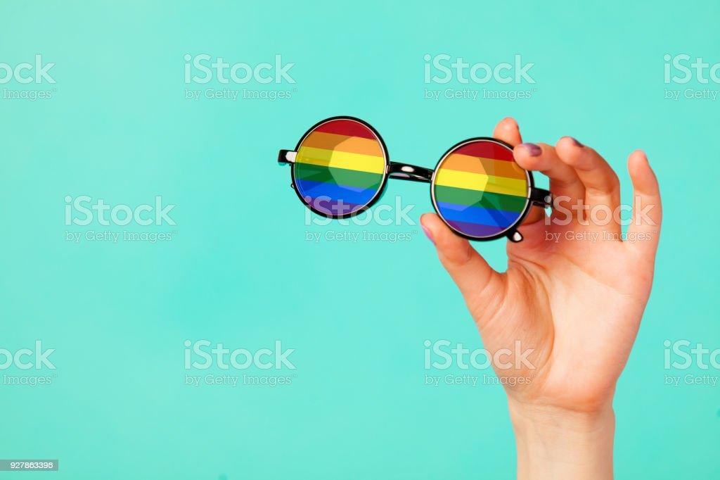 Female hand holding glasses with rainbow flag stock photo
