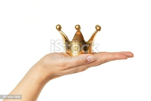 Female hand holding golden crown isolated on white background. Concept for success.
