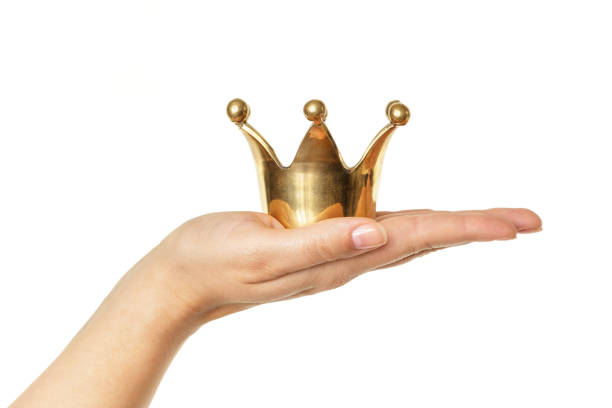 Female hand holding golden crown isolated on white background Female hand holding golden crown isolated on white background. Concept for success. abundance stock pictures, royalty-free photos & images