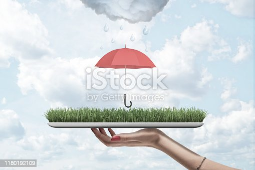 Female hand holding green grass board with red umbrella and rainy cloud above on blue sky background. People and objects. Digital art. Weather and forecast.